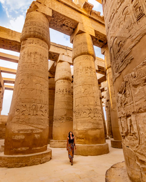 EXPLORING ANCIENT EGYPTIAN TEMPLES Young female traveller wandering through ancient Karnak Temple. Beautiful Egyptian landmark with hieroglyphics. Travelling woman adventuring around the world. Luxor, Egypt explorer stock pictures, royalty-free photos & images