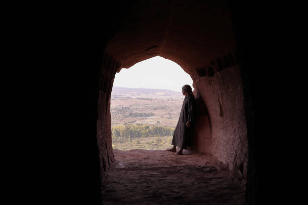 HERMIT MAN WITH ROBE IN THE ENTRANCE OF A OLD CAVE IN FRONT OF A VALLEY RESTING AND MEDITATING friar stock pictures, royalty-free photos & images