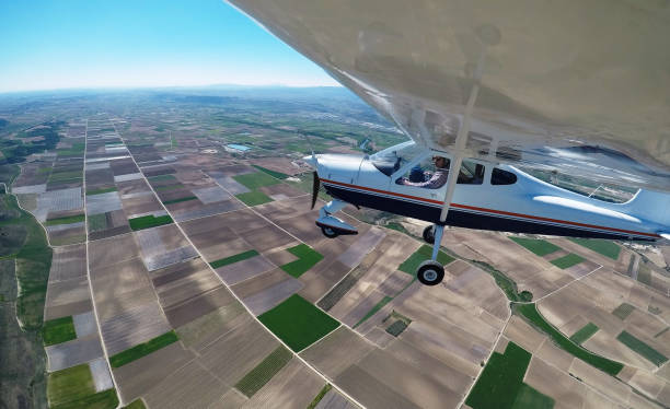 PILOT FLYING OVER  CULTIVATION FIELDS WITH A MONOMOTOR AIRPLANE stock photo