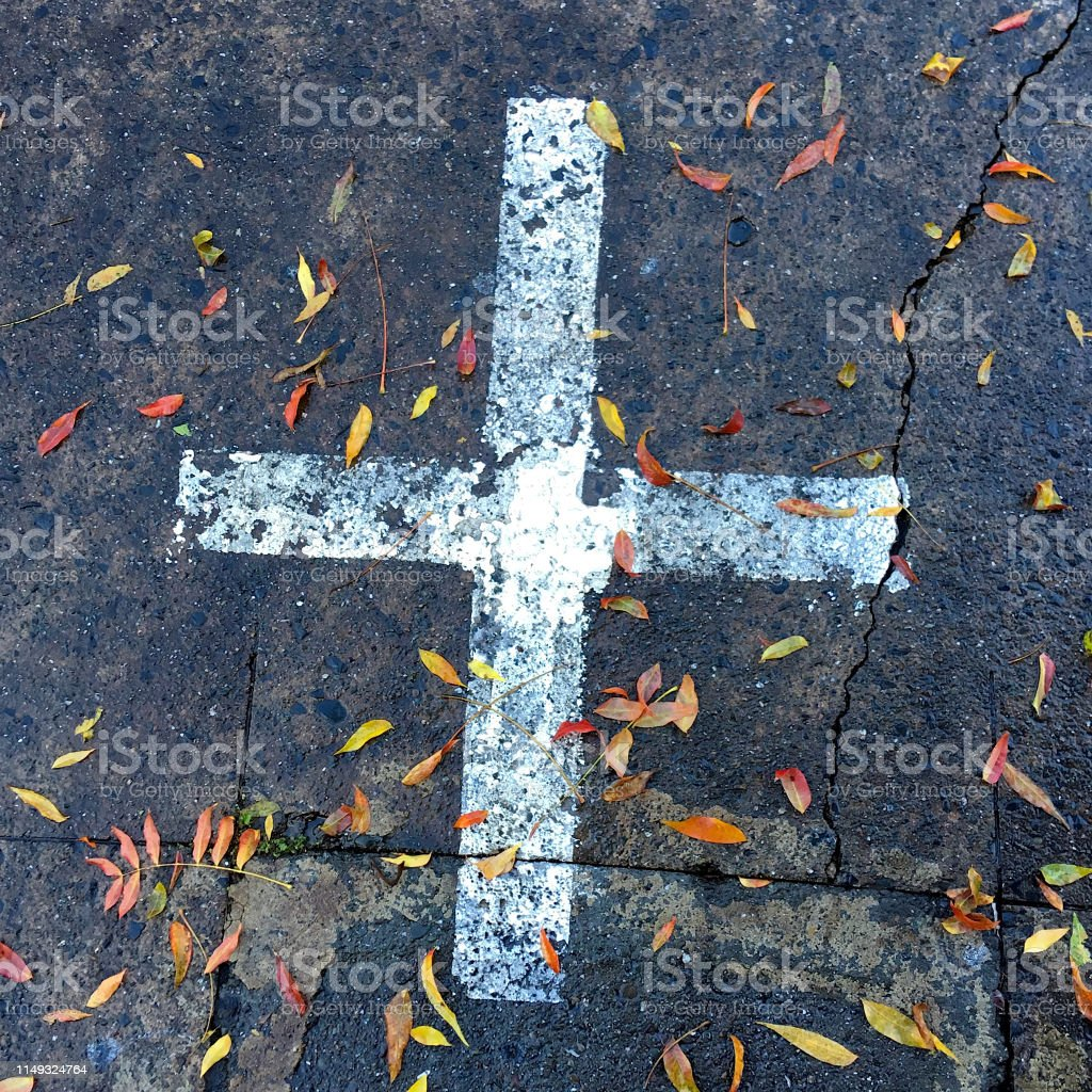 PAINTED CROSS AND LEAVES ON ROAD stock photo