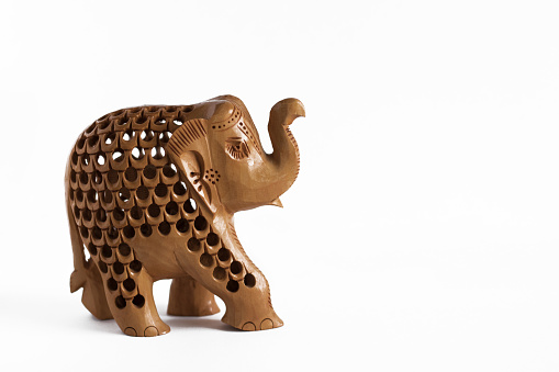 ELEPHANT FIGURE CARVED OUT OF WOOD, CLOSEUP ON WHITE BACKGROUND