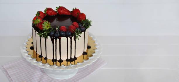homemade summer cake decorated mit icing chocolate, fresh raspberries, strawberries against white wooden background. - himbeerzuckerguss stock-fotos und bilder