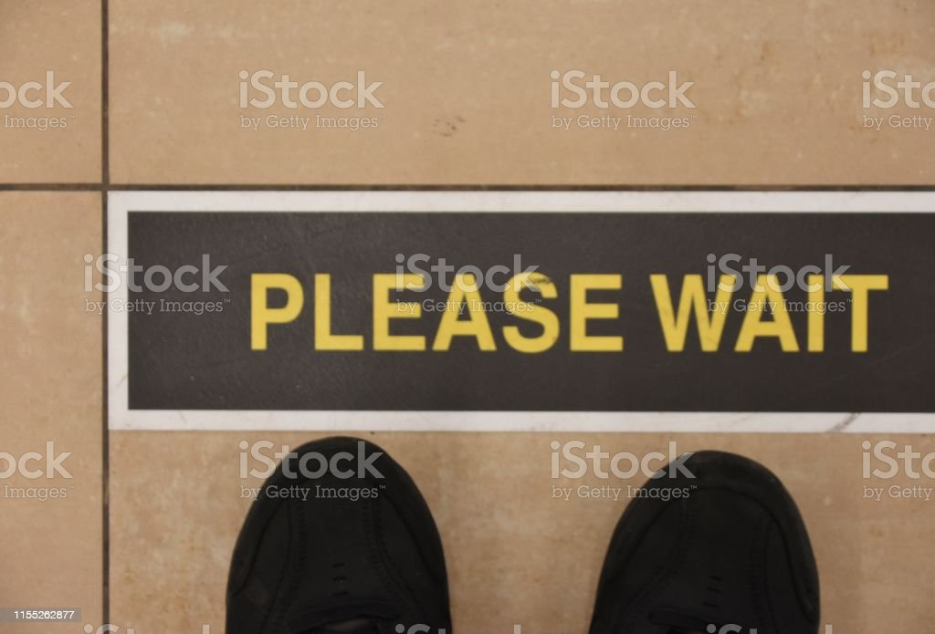 PLEASE WAIT- SIGN PLEASE WAIT- SIGN Airport Stock Photo