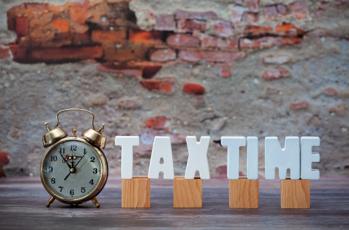 Concrete word TAX TIME uppercase with plaster texture with a clock and wooden blocks. Write the tax year.