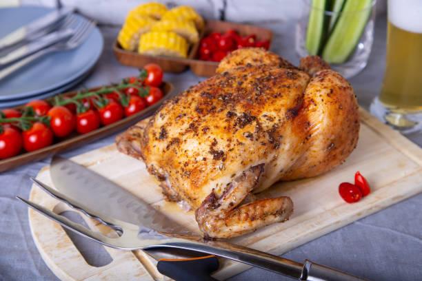 курица целиком запеченная на соли. с овощами. - girarrosto foto e immagini stock