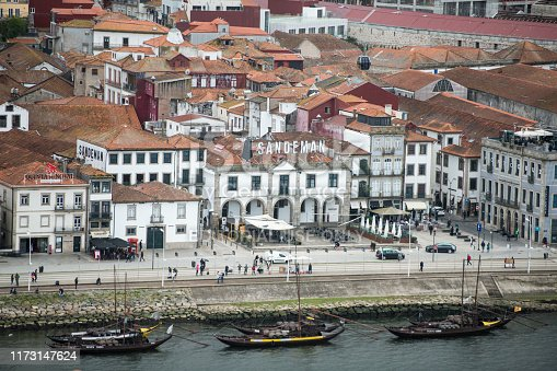 one of the Sandeman Port wine Cellar Buildings at the waterfront on the Douro River in Ribeira in the city centre of Porto in Porugal in Europe.  Portugal, Porto, April, 2019