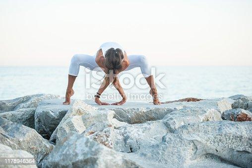 Mid Adult Woman on the Rocky Beach Practicing Yoga Spider Pose (Utkata Konasana)