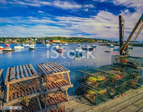 LOBSTER BASKET ON DOCK WITH CALM HARBOR WATERS AT BASS HARBOR, MAINE