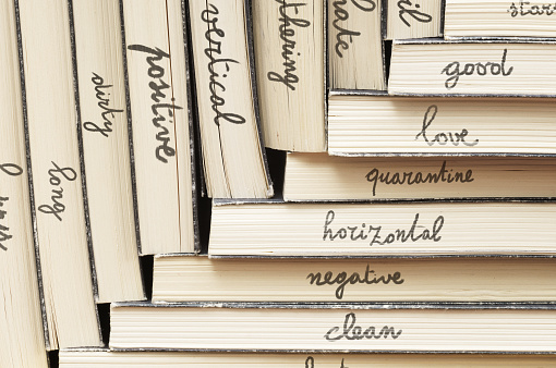 Words and their opposite (antonyms) are written on the sides of stacked books with a pencil by hand. *** The text was digitally added and a release is provided ***