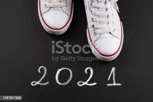White sneakers on blackboard with 2021