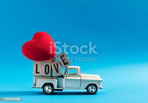 retro toy car delivering over burdened wooden cubes with text ' LOVE ' and big red heart shape for Valentine's day on blue background.