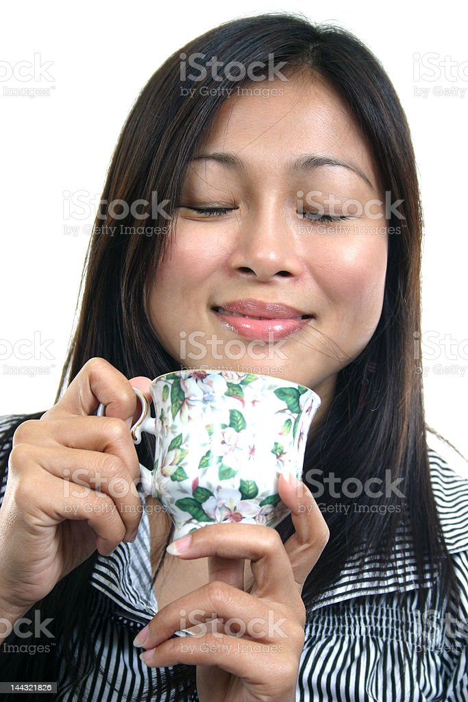 YOUNG ASIAN WOMAN ENJOYING TEA 2 royalty-free stock photo