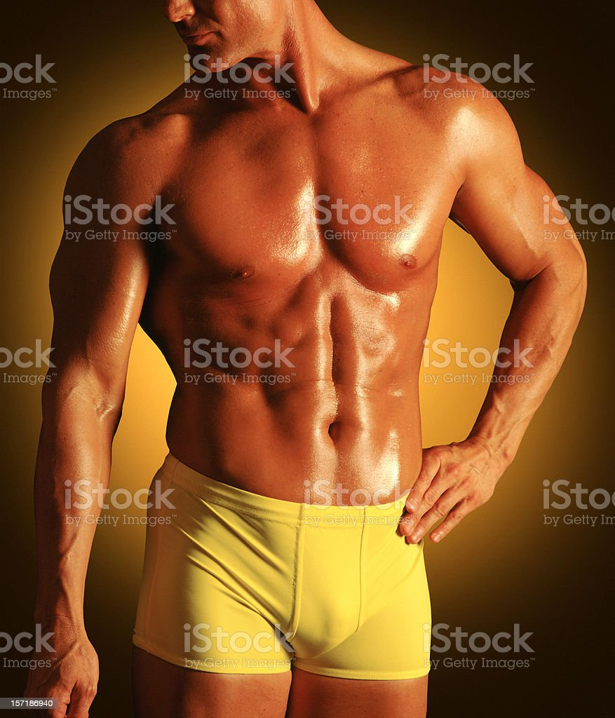 MUSCULAR MALE IN YELLOW TRUNKS royalty-free stock photo