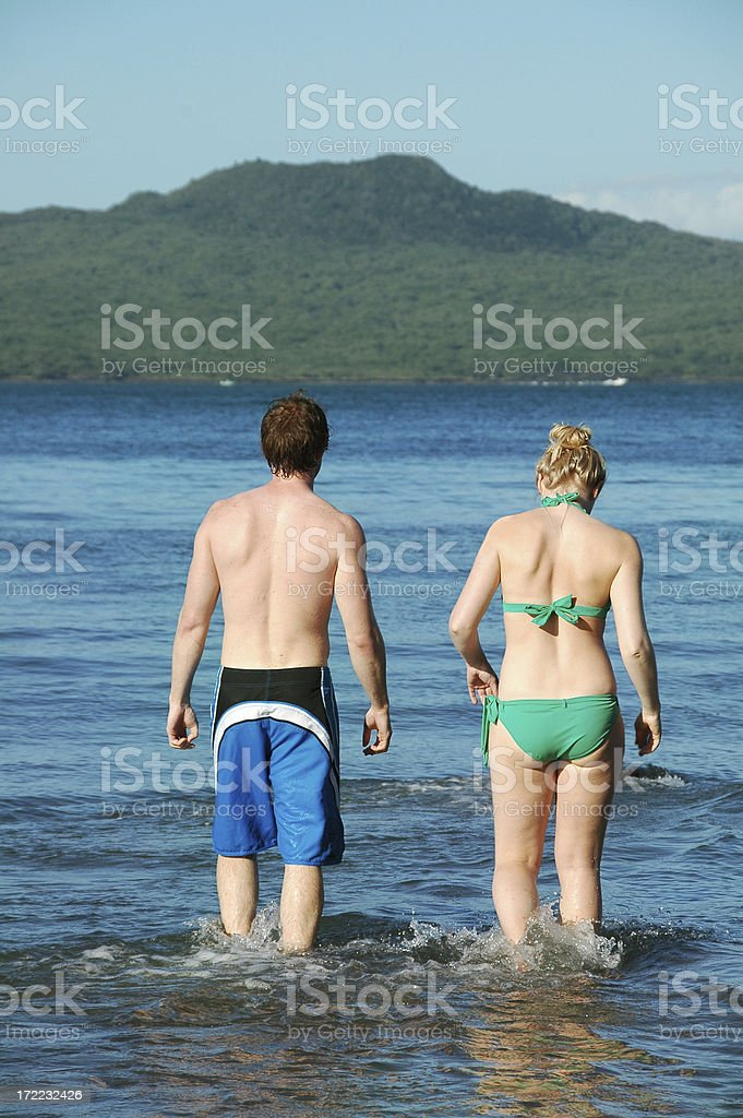 YOUNG COUPLE WALK INTO THE SEA royalty-free stock photo