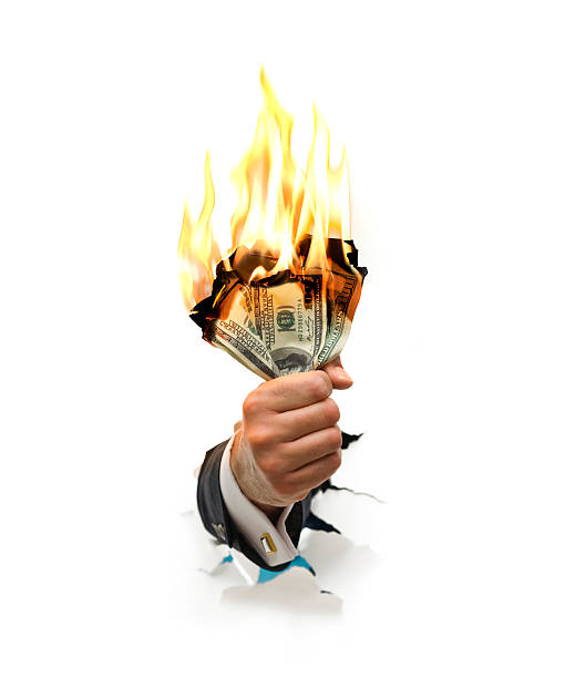 MONEY TO BURN A wealthy businessman's hand holding a wad of burning $100 bills money to burn stock pictures, royalty-free photos & images