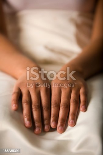 The hands of a young black woman at rest on cream satin