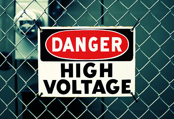 """DANGER HIGH VOLTAGE Metal """"DANGER HIGH VOLTAGE"""" sign tied to a fence. Shallow depth of field with electricity meter in the background. Simulated cross-processed effect. high voltage sign stock pictures, royalty-free photos & images"""