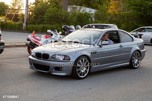 Dartmouth, Nova Scotia, Canada - June 6, 2013: A BMW M3 E46 driving into a parking lot.  Driver visible through window.  In background, some other cars and motorcycles are visible.  The E46 M3 was first introduced in 2000 and features 333 HP from a 3.2 litre engine.  The BMW M3 is considered one of the best sports cars of all time and is a benchmark in sports performance.