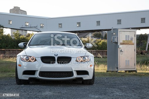 Halifax, Nova Scotia, Canada - June 27, 2015: Front view of a BMW M3 in an abandoned agricultural area.  This E92 BMW M3 sits on a gravel surface with parking lights turned on.  This is the fourth generation of the M3.