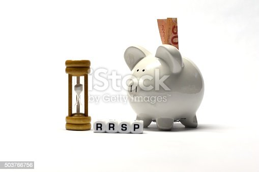 The Letter dices RRSP next to a white ceramic piggybank and a wooden hourglass. A fifty dollar banknote is inserted into the piggybank's slot.