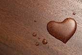 water drop heart on wooden table ; shot with very shallow depth of field