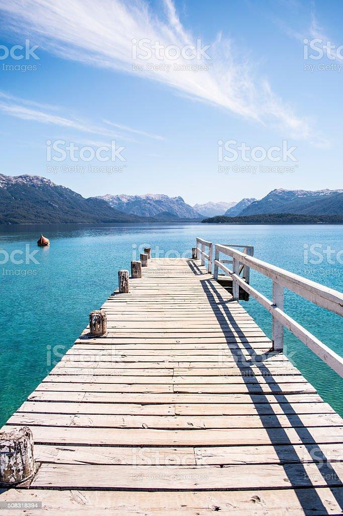 WOOD DOCK, LAKE AND MOUNTAIN RANGE stock photo
