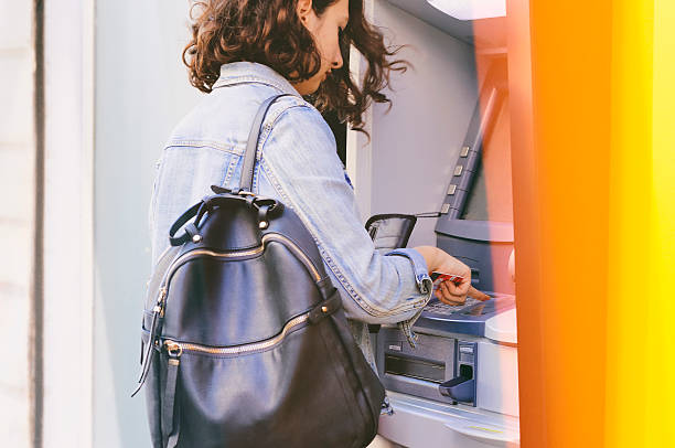 ATM Woman using credit card withdrawing money from an ATM machine outside a branch of savings bank. banks and atms stock pictures, royalty-free photos & images