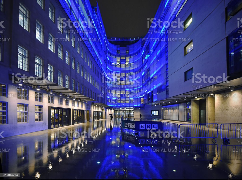 BBC HQ London, UK - March 24th 2016: BBC Broadcasting House in central London. Headquarters and offices of the British Broadcasting Corporation. Night time floodlit offices reflected in the rain - photographed from the public highway. BBC Stock Photo