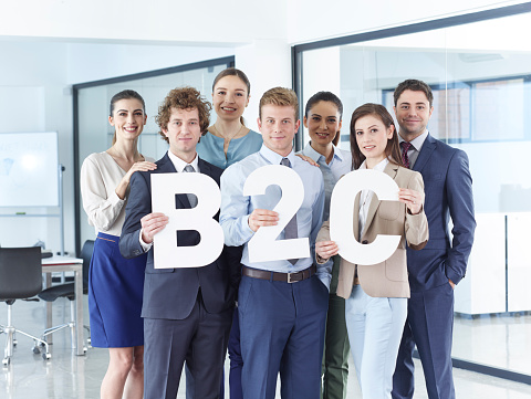 Business men and business women standing in office and holding letters.