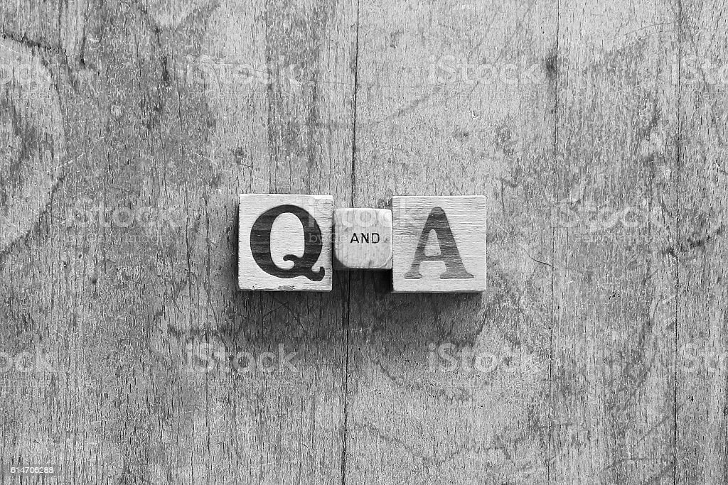 """Q&A Over head black and white image of vintage wooden dice printed with the letters """"Q  AND  A"""". Business Stock Photo"""