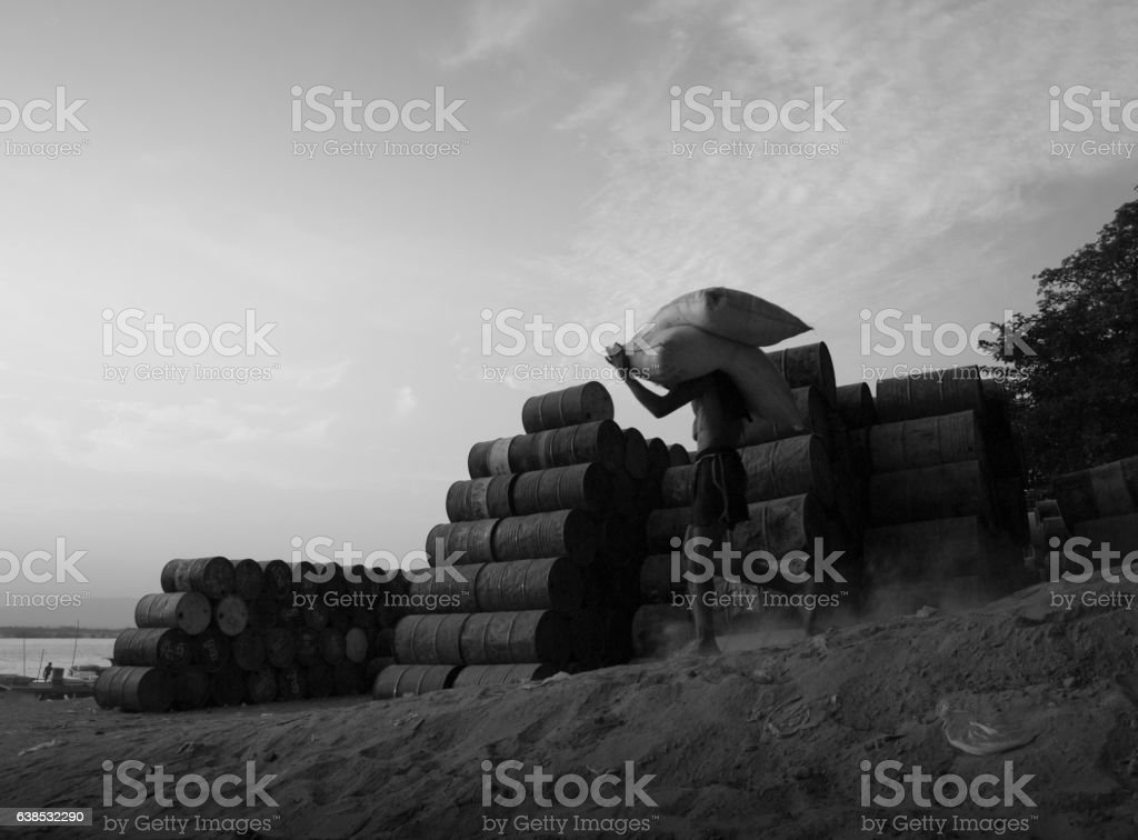 WORKER CARRYING SACKS ON SHOULDER stock photo