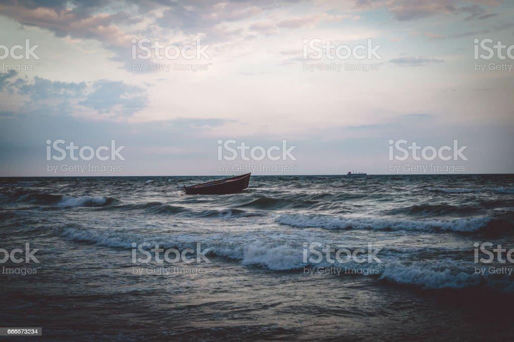 Морской пейзаж. Рыбацкая лодка и морской прибой stock photo