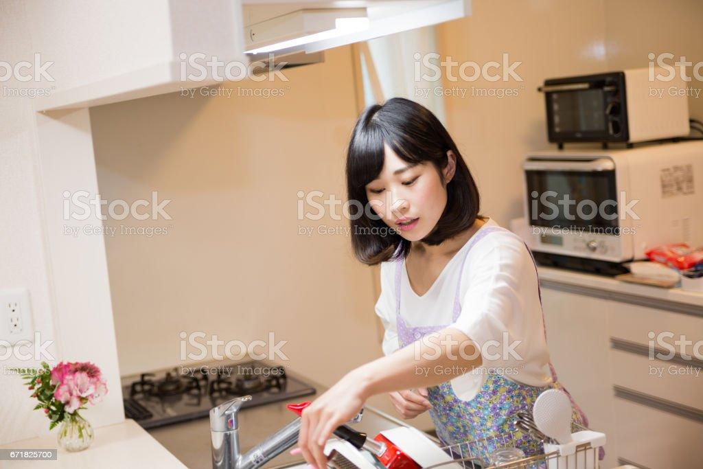 明るいキッチンに立つ日本人女性 stock photo