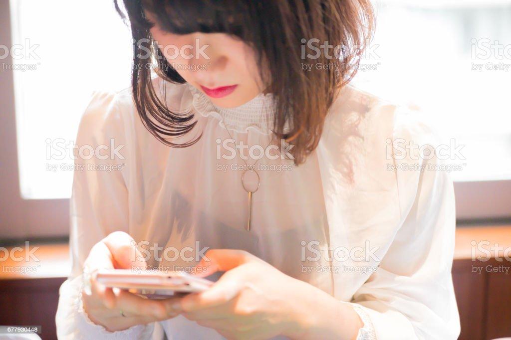 スマホを操作する可愛い 女性 stock photo