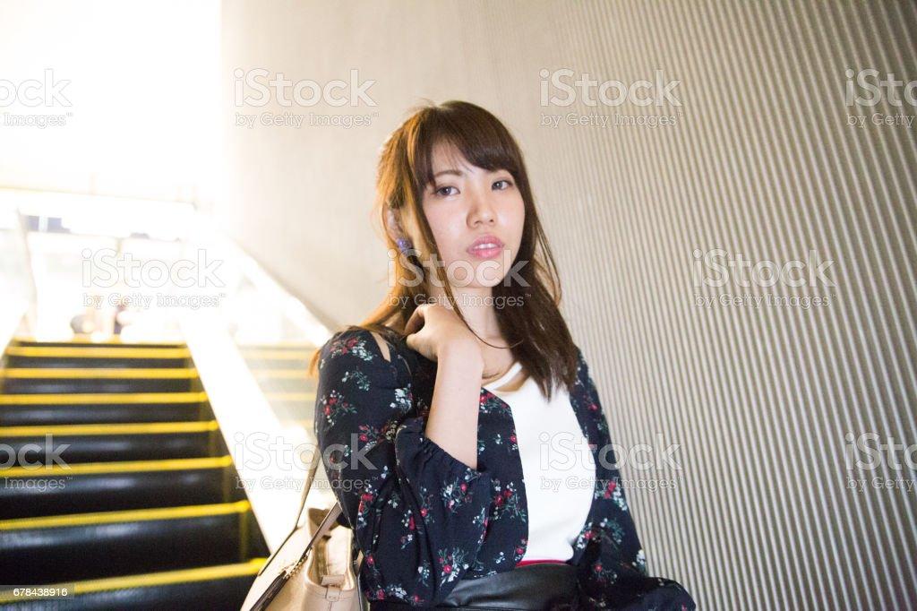 エスカレーターに乗る可愛い女性 royalty-free stock photo