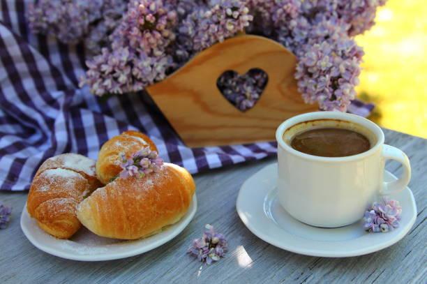 чашка кофе с букетом сирени - heiße schokoladen cupcakes stock-fotos und bilder