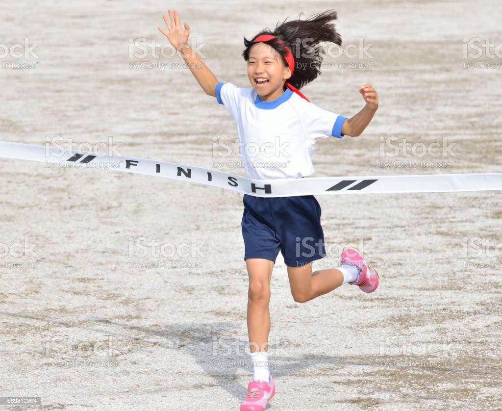 走る女の子(体操服、ゴールテープ) stock photo