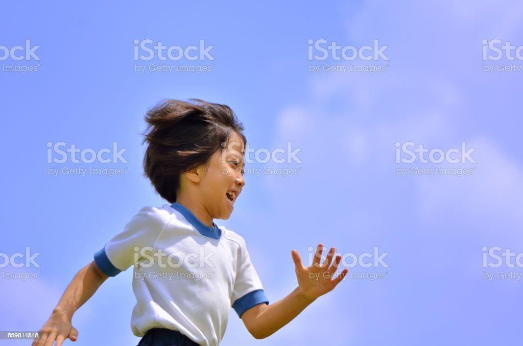 青空で走る女の子(体操服) stock photo