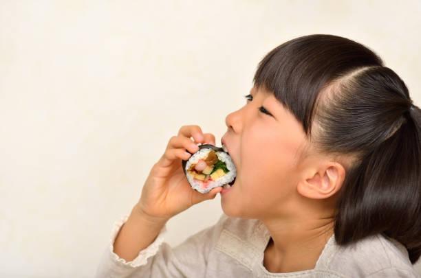 お寿司を食べる女の子 - sushi essen stock-fotos und bilder