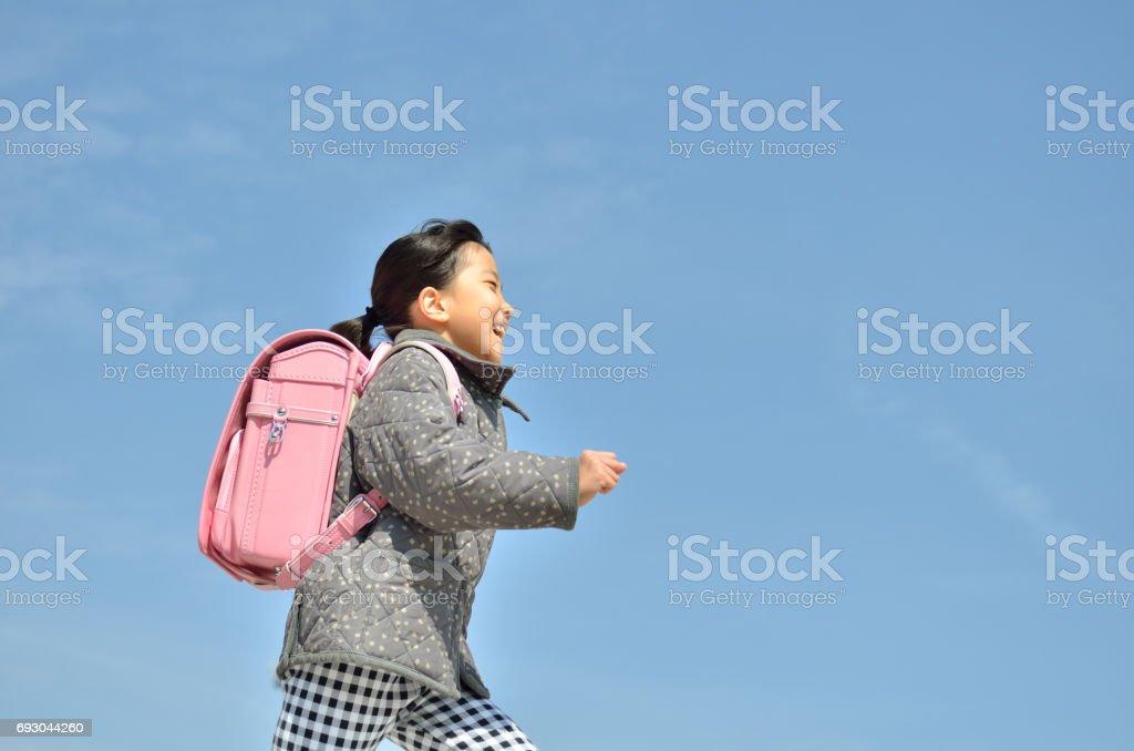 青空で走る女の子(ランドセル) ストックフォト