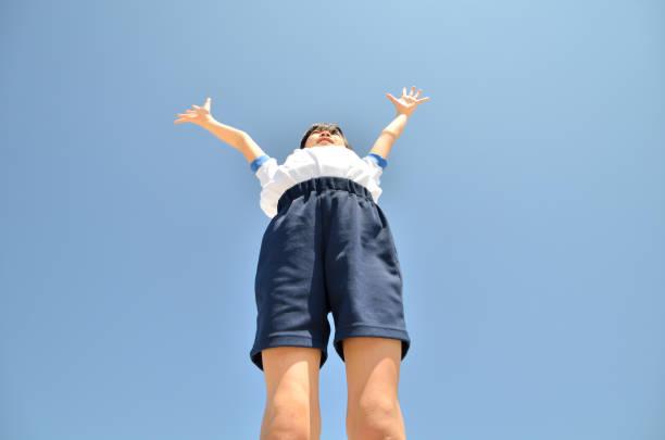 青空で見上げる女の子(体操服) stock photo
