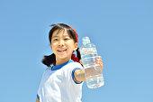 青空で水を飲む女の子(体操服、ハチマキ)