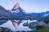 Early morning dawn scene of sunrise on the Matterhorn Mountain reflecting pink in the lake with male man on rock with red down jacket with clear blue sky Gornergrat Zermatt Matterhorn Europe