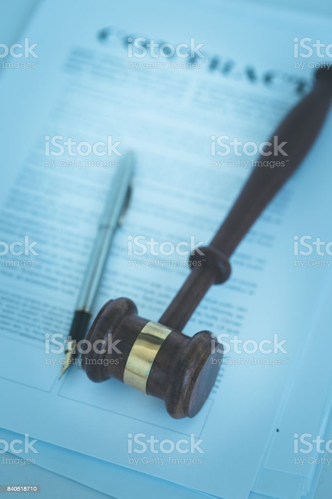 WOODEN JUDGE GAVEL WITH CONTRACT DOCUMENT AND PEN CONCEPT stock photo