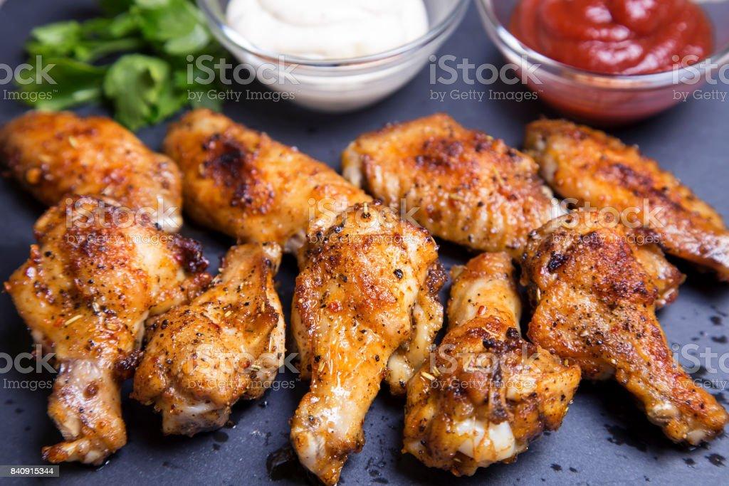 Куриные крылышки барбекю с двумя соусами на черной доске. stock photo