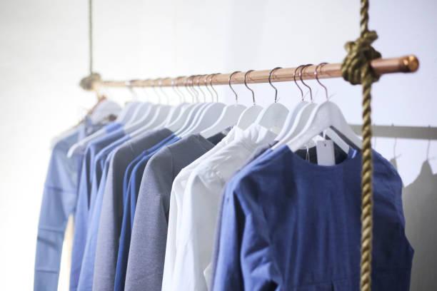 kleiderbügel mit kleidung - garderobenhaken stock-fotos und bilder