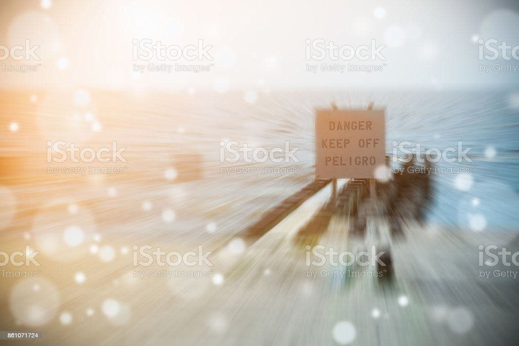 WARNING SIGN IN SPANISH 'DANGER KEEP OFF PELIGRO' ON BREAKWATER IN A BEACH WITH NICE BOKEH LIGHT stock photo
