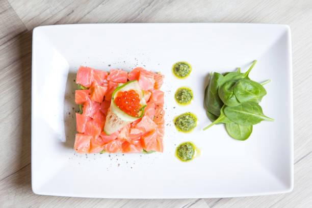тартар из лосося, икры и авокадо с соусом песто и шпинатом. - cimbaal stockfoto's en -beelden