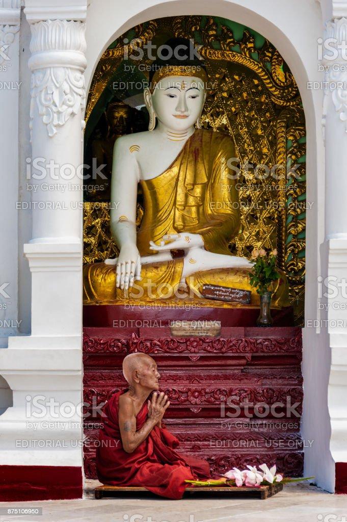 BUDDHIST MONK PRAYING AT SHWEDAGON PAGODA stock photo