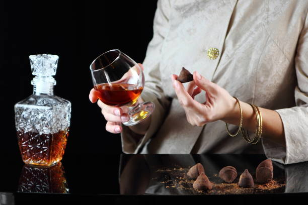 девушка с бокалом коньяка - schokoladen trüffeltorte stock-fotos und bilder